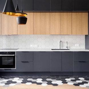Пример оригинального дизайна: отдельная, угловая кухня среднего размера в современном стиле с врезной раковиной, плоскими фасадами, белым фартуком, светлыми деревянными фасадами, столешницей из кварцевого композита, фартуком из керамогранитной плитки, черной техникой, полом из керамогранита, островом, разноцветным полом и серой столешницей