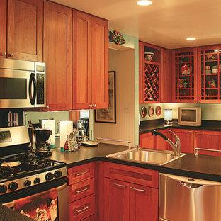 ワシントンD.C.の小さいコンテンポラリースタイルのおしゃれなキッチン (淡色無垢フローリング、アイランドなし、ドロップインシンク、落し込みパネル扉のキャビネット、茶色いキャビネット、ラミネートカウンター、シルバーの調理設備の、茶色い床) の写真