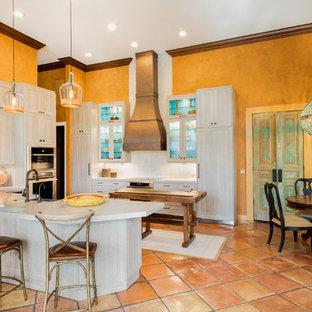 マイアミの中くらいのサンタフェスタイルのおしゃれなキッチン (シェーカースタイル扉のキャビネット、セラミックタイルのキッチンパネル、シルバーの調理設備、テラコッタタイルの床、オレンジの床、エプロンフロントシンク、白いキャビネット、白いキッチンパネル、白いキッチンカウンター) の写真