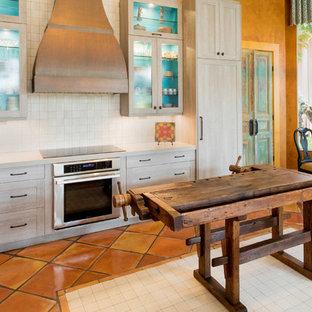 マイアミの中くらいのサンタフェスタイルのおしゃれなキッチン (アンダーカウンターシンク、シェーカースタイル扉のキャビネット、淡色木目調キャビネット、マルチカラーのキッチンパネル、セラミックタイルのキッチンパネル、シルバーの調理設備、テラコッタタイルの床) の写真