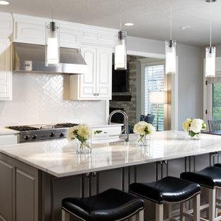 Foto på ett stort vintage kök, med en undermonterad diskho, luckor med upphöjd panel, vita skåp, bänkskiva i kvarts, vitt stänkskydd, stänkskydd i tunnelbanekakel, rostfria vitvaror, mörkt trägolv och en köksö