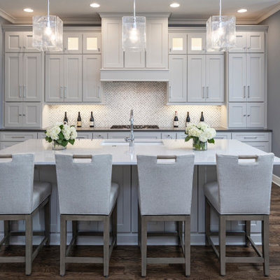 Large transitional l-shaped brown floor and dark wood floor open concept kitchen photo in Kansas City with an undermount sink, shaker cabinets, white cabinets, quartzite countertops, mosaic tile backsplash, stainless steel appliances, an island, white backsplash and gray countertops