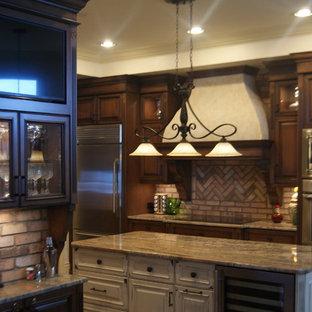 ジャクソンビルのトラディショナルスタイルのおしゃれなアイランドキッチン (ダブルシンク、レイズドパネル扉のキャビネット、中間色木目調キャビネット、御影石カウンター、ピンクのキッチンパネル、レンガのキッチンパネル、シルバーの調理設備の、テラコッタタイルの床) の写真