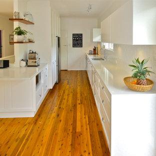 Inspiration for a mid-sized modern galley eat-in kitchen in Sydney with an undermount sink, shaker cabinets, white cabinets, quartz benchtops, white splashback, terra-cotta splashback, stainless steel appliances and medium hardwood floors.
