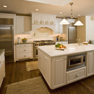 Traditional enclosed kitchen pictures - Example of a classic enclosed kitchen design in San Francisco with raised-panel cabinets, stainless steel appliances, a farmhouse sink, white cabinets and multicolored backsplash