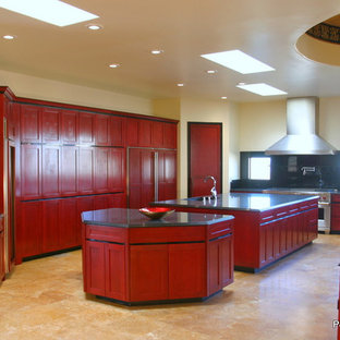 Design ideas for an expansive world-inspired u-shaped kitchen pantry in Albuquerque with a submerged sink, shaker cabinets, red cabinets, black splashback, stainless steel appliances, travertine flooring, multiple islands, granite worktops, stone slab splashback and beige floors.
