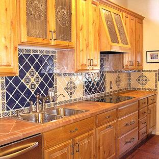 Удачное сочетание для дизайна помещения: линейная кухня-гостиная среднего размера в классическом стиле с накладной раковиной, фасадами с выступающей филенкой, фасадами цвета дерева среднего тона, синим фартуком, фартуком из керамической плитки, техникой из нержавеющей стали, кирпичным полом, островом и красным полом - самое интересное для вас