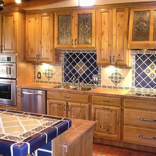 На фото: линейные кухни-гостиные среднего размера в классическом стиле с накладной раковиной, фасадами с выступающей филенкой, фасадами цвета дерева среднего тона, синим фартуком, фартуком из керамической плитки, техникой из нержавеющей стали, кирпичным полом, островом и красным полом