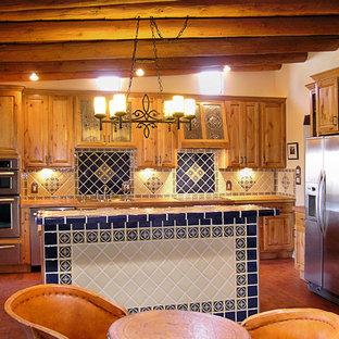 Foto på ett mellanstort amerikanskt linjärt kök med öppen planlösning, med en nedsänkt diskho, luckor med upphöjd panel, skåp i mellenmörkt trä, blått stänkskydd, stänkskydd i keramik, rostfria vitvaror, tegelgolv, en köksö och rött golv