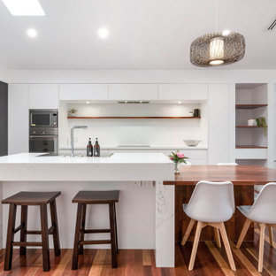 Inspiration for a contemporary l-shaped kitchen in Brisbane with flat-panel cabinets, white cabinets, white splashback, stainless steel appliances, dark hardwood floors, with island, brown floor, white benchtop and vaulted.
