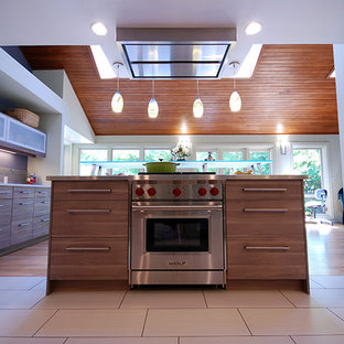 Photo of a mid-sized midcentury u-shaped open plan kitchen in San Francisco with an undermount sink, flat-panel cabinets, medium wood cabinets, zinc benchtops, brown splashback, ceramic splashback, stainless steel appliances, ceramic floors, with island and beige floor.