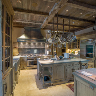 Design ideas for a large country galley open plan kitchen in Charlotte with a farmhouse sink, glass-front cabinets, distressed cabinets, limestone benchtops, porcelain splashback, stainless steel appliances and multiple islands.