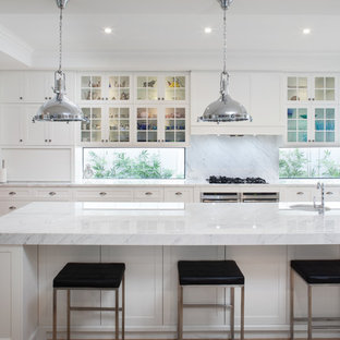 Photo of a transitional l-shaped kitchen in Perth with an undermount sink, glass-front cabinets, white cabinets, window splashback, stainless steel appliances, medium hardwood floors, with island and brown floor.