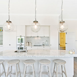 Design ideas for a transitional single-wall open plan kitchen in Perth with an undermount sink, shaker cabinets, white cabinets, grey splashback, stainless steel appliances, light hardwood floors, with island and grey floor.