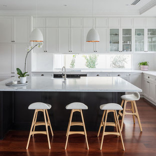 This is an example of a traditional l-shaped kitchen in Perth with a belfast sink, shaker cabinets, white cabinets, window splashback, medium hardwood flooring, an island and brown floors.