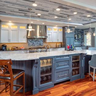 ボストンのビーチスタイルのおしゃれなキッチン (シェーカースタイル扉のキャビネット、白いキャビネット、ベージュキッチンパネル、サブウェイタイルのキッチンパネル、パネルと同色の調理設備、無垢フローリング、オレンジの床、黒いキッチンカウンター) の写真