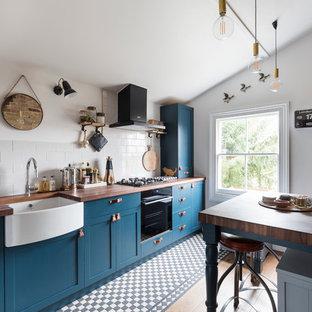 ロンドンのトランジショナルスタイルのおしゃれなI型キッチン (エプロンフロントシンク、シェーカースタイル扉のキャビネット、青いキャビネット、白いキッチンパネル、黒い調理設備、アイランドなし) の写真