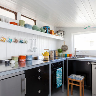 Scandi l-shaped kitchen in London with an integrated sink, flat-panel cabinets, black cabinets, stainless steel worktops, white splashback and stainless steel appliances.