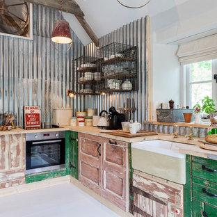 Industrial Küche in L-Form mit Landhausspüle, Schränken im Used-Look, Arbeitsplatte aus Holz, Küchenrückwand in Metallic und Rückwand aus Metallfliesen in London