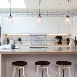 Design ideas for a transitional galley kitchen in London with an integrated sink, flat-panel cabinets, white cabinets, white splashback, subway tile splashback and with island.