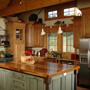 サンディエゴの中くらいのトラディショナルスタイルのおしゃれなキッチン (エプロンフロントシンク、レイズドパネル扉のキャビネット、中間色木目調キャビネット、木材カウンター、シルバーの調理設備、テラコッタタイルの床、赤い床) の写真