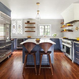 Exemple d'une cuisine chic en U avec un évier de ferme, un placard avec porte à panneau encastré, des portes de placard violettes, une crédence blanche, un électroménager en acier inoxydable, un sol en bois brun, un îlot central, un sol marron et un plan de travail blanc.