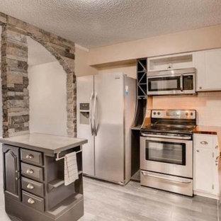 デンバーの中サイズのトランジショナルスタイルのおしゃれなキッチン (エプロンフロントシンク、フラットパネル扉のキャビネット、白いキャビネット、木材カウンター、白いキッチンパネル、サブウェイタイルのキッチンパネル、シルバーの調理設備の、クッションフロア、グレーの床、茶色いキッチンカウンター) の写真