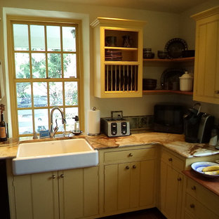 Small farmhouse eat-in kitchen appliance - Small country single-wall eat-in kitchen photo in Philadelphia with a farmhouse sink, flat-panel cabinets, yellow cabinets, granite countertops, multicolored backsplash, ceramic backsplash, black appliances and no island