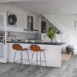 Small eclectic kitchen in Denver with flat-panel cabinets, white cabinets, porcelain splashback, stainless steel appliances, porcelain floors, a peninsula and grey floor.