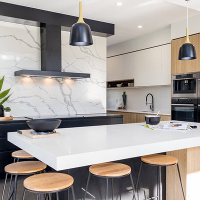 Inspiration for a contemporary concrete floor and gray floor open concept kitchen remodel in Sunshine Coast with an undermount sink, flat-panel cabinets, black cabinets, quartz countertops, an island, white backsplash, stone slab backsplash, stainless steel appliances and white countertops