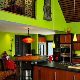 デンバーの中サイズのアジアンスタイルのおしゃれなキッチン (フラットパネル扉のキャビネット、中間色木目調キャビネット、人工大理石カウンター、緑のキッチンパネル、シルバーの調理設備の、セラミックタイルの床、茶色い床) の写真
