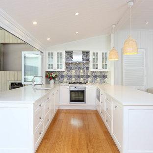 Offene, Mittelgroße Klassische Küche ohne Insel in U-Form mit Unterbauwaschbecken, Schrankfronten im Shaker-Stil, weißen Schränken, Küchenrückwand in Blau, Rückwand aus Mosaikfliesen, hellem Holzboden, Quarzwerkstein-Arbeitsplatte, Küchengeräten aus Edelstahl und weißer Arbeitsplatte in Brisbane