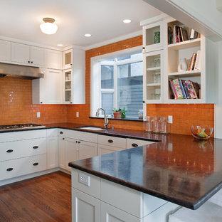シアトルのコンテンポラリースタイルのおしゃれなキッチン (シェーカースタイル扉のキャビネット、白いキャビネット、オレンジのキッチンパネル、サブウェイタイルのキッチンパネル、シングルシンク) の写真