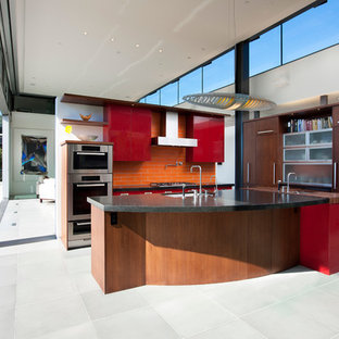 This is an example of a medium sized contemporary l-shaped open plan kitchen in Santa Barbara with a submerged sink, flat-panel cabinets, dark wood cabinets, granite worktops, orange splashback, metro tiled splashback, stainless steel appliances, cement flooring and an island.