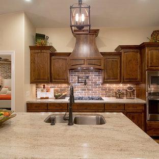 ソルトレイクシティの広いトラディショナルスタイルのおしゃれなキッチン (アンダーカウンターシンク、レイズドパネル扉のキャビネット、中間色木目調キャビネット、御影石カウンター、茶色いキッチンパネル、レンガのキッチンパネル、シルバーの調理設備、クッションフロア) の写真