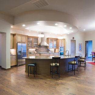 Design ideas for a mid-sized contemporary single-wall open plan kitchen in Albuquerque with an undermount sink, glass-front cabinets, light wood cabinets, multi-coloured splashback, stainless steel appliances, plywood floors and with island.