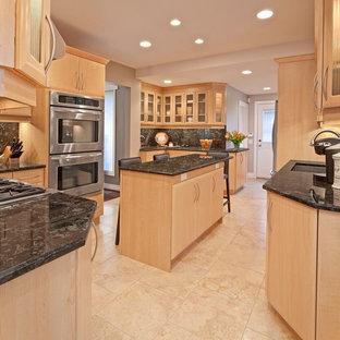 トロントの大きいトラディショナルスタイルのおしゃれなキッチン (アンダーカウンターシンク、フラットパネル扉のキャビネット、淡色木目調キャビネット、御影石カウンター、黒いキッチンパネル、石スラブのキッチンパネル、シルバーの調理設備の、クッションフロア) の写真