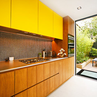 Midcentury modern eat-in kitchen ideas - 1950s single-wall porcelain floor eat-in kitchen photo in Gloucestershire with yellow cabinets, stainless steel countertops, black backsplash, mosaic tile backsplash and stainless steel appliances