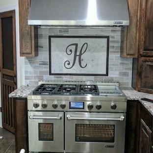 オースティンのトランジショナルスタイルのおしゃれなキッチン (レイズドパネル扉のキャビネット、中間色木目調キャビネット、御影石カウンター、マルチカラーのキッチンパネル、サブウェイタイルのキッチンパネル、シルバーの調理設備、ラミネートの床、茶色い床、マルチカラーのキッチンカウンター) の写真