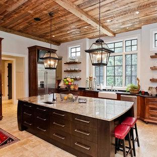 Große Urige Küche in L-Form mit Vorratsschrank, Landhausspüle, Schrankfronten mit vertiefter Füllung, beigen Schränken, Granit-Arbeitsplatte, Küchenrückwand in Beige, Rückwand aus Steinfliesen, Küchengeräten aus Edelstahl, Travertin und Kücheninsel in Sonstige