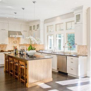 На фото: с высоким бюджетом угловые кухни среднего размера в классическом стиле с фасадами в стиле шейкер, белыми фасадами, бежевым фартуком, фартуком из удлиненной плитки, техникой из нержавеющей стали, темным паркетным полом, островом, обеденным столом, одинарной раковиной, столешницей из акрилового камня, коричневым полом и серой столешницей