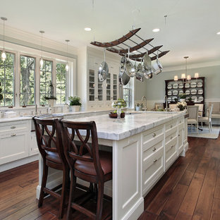 Inspiration for a large shabby-chic style galley medium tone wood floor open concept kitchen remodel in Los Angeles with a drop-in sink, raised-panel cabinets, white cabinets, stainless steel appliances, marble countertops, white backsplash, ceramic backsplash, an island and gray countertops