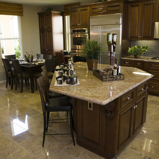 Inspiration for a mid-sized arts and crafts galley eat-in kitchen in Los Angeles with a double-bowl sink, shaker cabinets, dark wood cabinets, granite benchtops, stainless steel appliances, marble floors and with island.