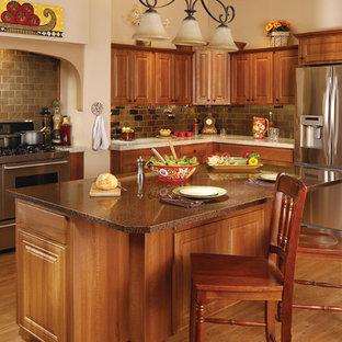 Große Klassische Küche in L-Form mit profilierten Schrankfronten, hellbraunen Holzschränken, Granit-Arbeitsplatte, bunter Rückwand, Rückwand aus Schiefer, Küchengeräten aus Edelstahl, hellem Holzboden, Kücheninsel und braunem Boden in Tampa