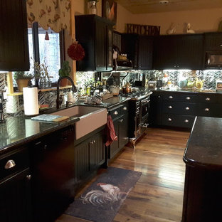 フェニックスの小さいヴィクトリアン調のおしゃれなキッチン (落し込みパネル扉のキャビネット、緑のキャビネット、エプロンフロントシンク、御影石カウンター、ガラスタイルのキッチンパネル、黒い調理設備、無垢フローリング) の写真
