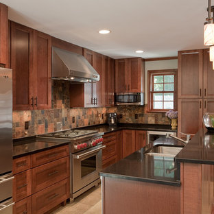 ワシントンD.C.の中サイズのエクレクティックスタイルのおしゃれなキッチン (ダブルシンク、シェーカースタイル扉のキャビネット、濃色木目調キャビネット、御影石カウンター、茶色いキッチンパネル、スレートのキッチンパネル、シルバーの調理設備、磁器タイルの床、ベージュの床) の写真