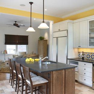 ワシントンD.C.の大きいエクレクティックスタイルのおしゃれなキッチン (パネルと同色の調理設備、アンダーカウンターシンク、シェーカースタイル扉のキャビネット、白いキャビネット、ソープストーンカウンター、マルチカラーのキッチンパネル、磁器タイルのキッチンパネル、トラバーチンの床、ベージュの床) の写真