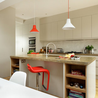 Inspiration for a mid-sized contemporary galley eat-in kitchen in Other with flat-panel cabinets, beige cabinets, beige splashback, stainless steel appliances, multiple islands, brown floor, an integrated sink and light hardwood floors.