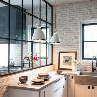 Exemple d'une cuisine industrielle fermée et de taille moyenne avec un évier de ferme, un placard à porte plane, des portes de placard blanches, un plan de travail en surface solide, une crédence blanche, une crédence en brique, un sol en bois brun et un sol marron.