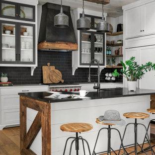 На фото: угловая кухня-гостиная среднего размера в стиле кантри с раковиной в стиле кантри, фасадами в стиле шейкер, белыми фасадами, столешницей из кварцевого агломерата, черным фартуком, фартуком из керамической плитки, техникой под мебельный фасад, паркетным полом среднего тона, островом, коричневым полом, черной столешницей и деревянным потолком с